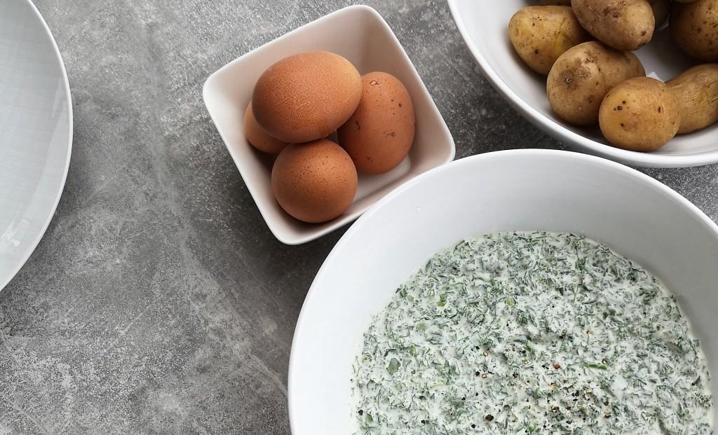 In drei weißen Schalen auf einem Tisch befinden sich Eier, Kartoffeln und Frankfurter Grüne Soße